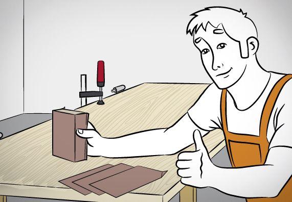 Heimwerker mit Schleifklotz und Schleifpapier vor Werkbank.