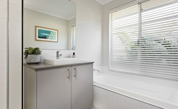 The main bathroom offers a semi-inset vanity basin, bath and shower