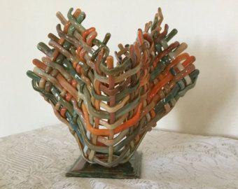Questo vaso unico tessuto vetro fuso viene fatto più mano Taglia strisce di vetro. Sono stati accuratamente assemblati, accasciati, tessute e tack fusa, poi si accasciò nuovamente al fine di ottenere le pieghe belle nel bicchiere. I colori nella trama sono tonalità di viola e mirtillo. Questo vaso scultura non reggerà, ma può essere riempito con fiori secchi, visualizzati come un supporto di candela o un pezzo darte a sé stante.  Misura 7 3/4 di altezza e 7 wide. È collegato a una base…