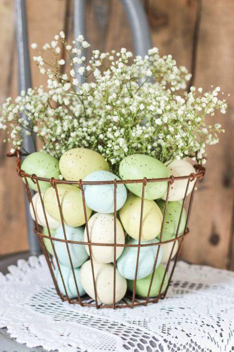 Ostern-Blumen-Drahtkorb mit Pastelleiern und Baby-Atem