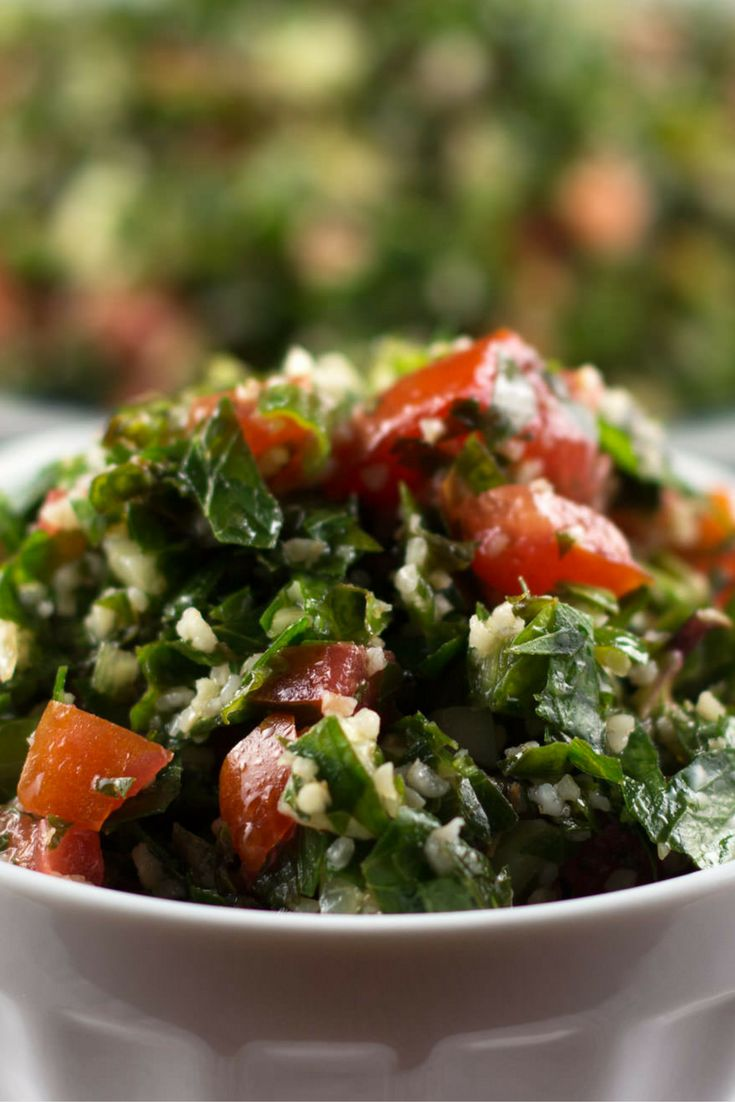 Simple, refreshing and perfect for a party or large family dinner. Not Quite Traditional Tabouli Salad - made with lots of greens, chopped tomato and cucumber and a handful of bulgur wheat.