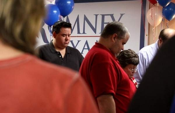 Patrick Hopper and other Mitt Romney supporters pray at the Election Night GOP Party hosted by the Madison County Republican Party at the All Suites Hotel in Jackson, Tuesday, November 6, 2012