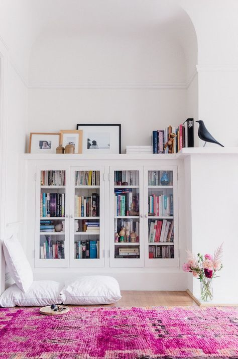 Built in book shelves with cozy pillows on the floor