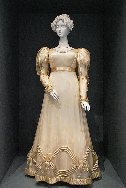 Europe, c 1825 • Silk net with silk embroidery and silk satin trim • During the Romantic era, sleeves began to widen, waistlines dropped slightly, and skirts flared out at the hem. The fashionable hourglass silhouette was enhanced by details on the upper and lower areas of dresses. Here, the satin trim on the sleeves and the undulating tubular trim (rouleau) on the skirt emphasize volume, while the transparent fabric gives ghe impression of a delicate lightness.