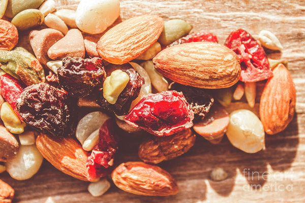 Trail mix high-energy snack food background with a nutritious mixture of nuts, seeds, kernels, dried fruit and chocolate on a wooden surface in a close up view by Jorgo Photography - Wall Art Gallery