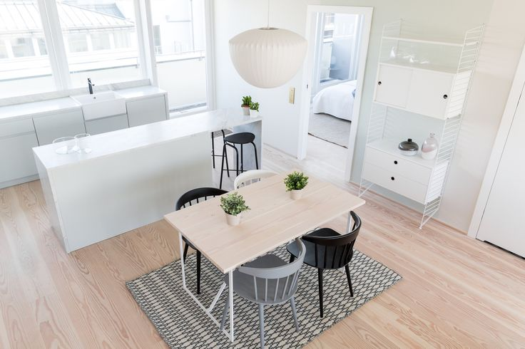Modern kitchen and dining area by Studio Mills complete with white marble counter and Dinesen flooring.