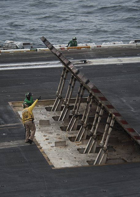 GULF OF OMAN (July 15, 2013) Sailors inspect a jet blast deflector on the flight deck of the aircraft carrier USS Nimitz (CVN 68). Nimitz Strike Group is deployed to the U.S. 5th Fleet area of responsibility conducting maritime security operations, theater security cooperation efforts and support missions for Operation Enduring Freedom. (U.S. Navy photo by Mass Communication Specialist 3rd Class Raul Moreno Jr./Released)