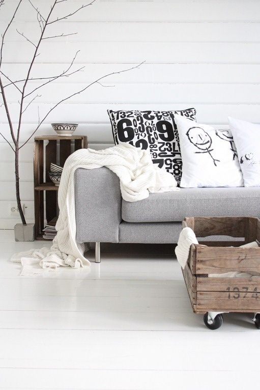 white scandinavian living room with a touch of nature.. Love the idea of getting kids to draw pictures on cushions...