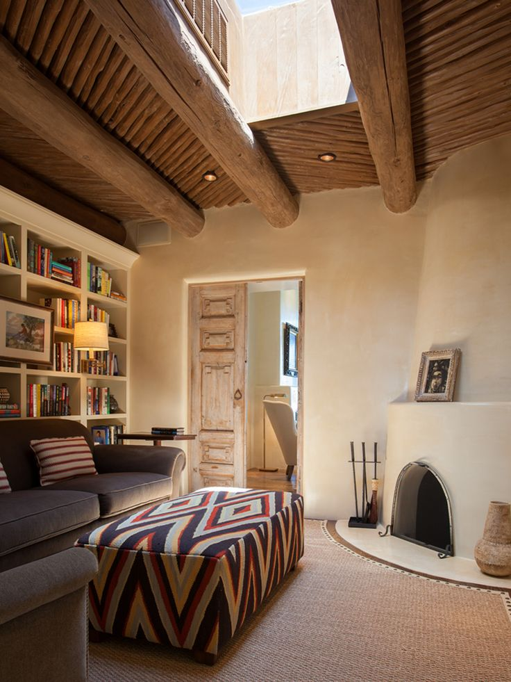This cozy sitting room off the master suite features classic Southwestern touches, such as a kiva fireplace, hand-plastered walls, and carved wooden doors. A stunning skylight brightens up the space during the day.    - CountryLiving.com