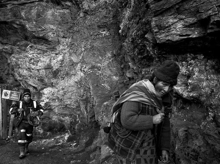 "Moises Saman  PERU. La Rinconada. February 28, 2015. A woman working as ""pallaquera"" walks past the entrance to a gold mine in Lunar de Oro, a mining town adjacent to La Rinconada."