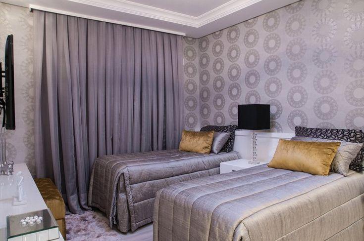 No quarto de hóspedes, foram colocadas duas camas de solteiro e móveis em tons neutros.