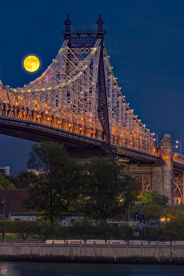 The full moon rises over the Queensboro Bridge in midtown Manhattan in New York City