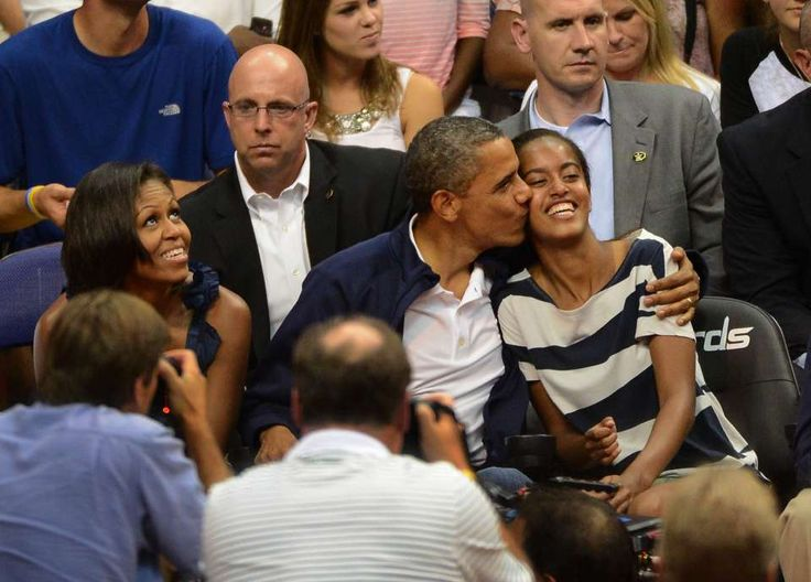 "President Barack Obama gives his daughter Malia Obama a hug and a kiss after not kissing his wife Michelle on ""Kiss Cam"" during an exhibition game against Brazil at the Verizon Center, July 16, 2012."