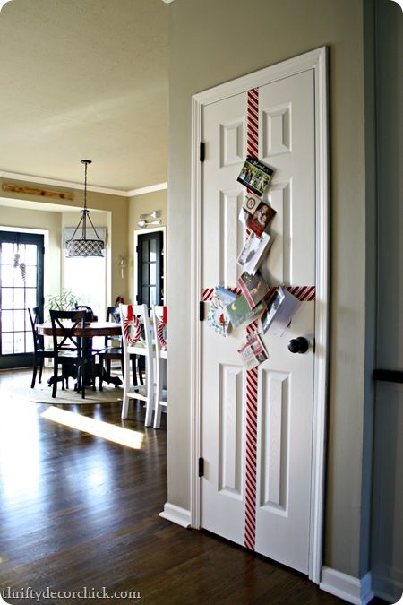 Thrifty Decor Chick: Easy, quick holiday card display - I did this today in a chevron/zigzag pattern across my accordion bi-fold laundry doors and it looks fantastic! Now the cards aren't cluttering up my fridge and counters.
