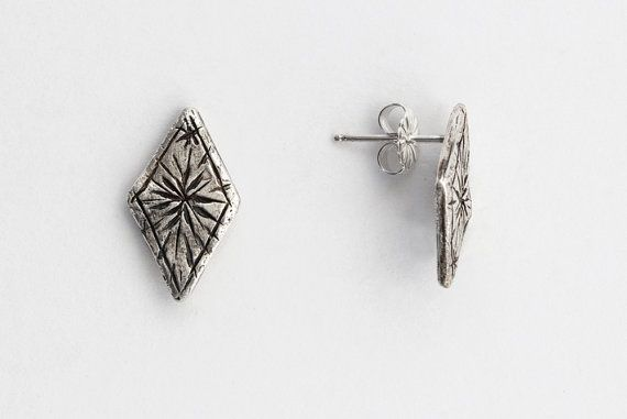 A pair of diamond-shaped studs, with radiating stars etched into them.    Approximately 3/4 inch tall. Posts and backs are sterling silver.    Also