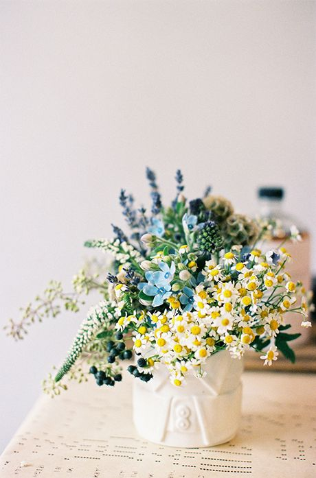 A blue and yellow feverfew and tweedia #centerpiece | Brides.com