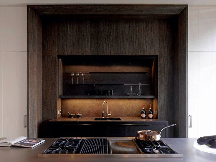 Who says minimal can't be rich? Not the design experts at Obumex. Shown here, a shock of chocolatey wood and stone create a luxe backdrop for cooking.