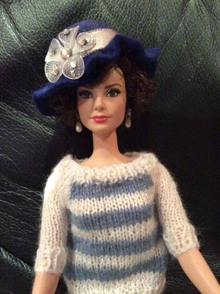 Audrey us wearing a hand knitted jumper and blue hat