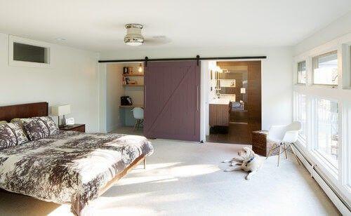 Dieses Master-Schlafzimmer und seine dunkle Pflaumen-Scheunentor zeigt die Vielseitigkeit der Tür. Wenn das Bad und die Rezeption Bereiche offen sein müssen, kann die Tür in der Mitte der Wand zwischen den beiden Zimmern ausruhen.