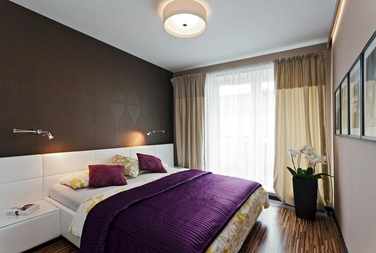 Tmavě hnědá stěna v kombinaci s fialovou, bílou a odstíny béžové dělají z ložnice nejelegantnější místnost v bytě.