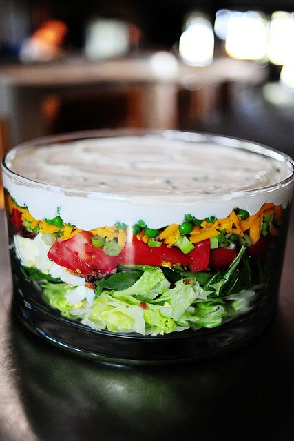 Pioneer Woman layered salad. Layer iceberg lettuce, tomato chunks, salt & pepper, spinach, hard boiled eggs, salt & pepper, bacon, green onions, shredded cheese, frozen peas rinsed and slightly thawed. Top with dressing.