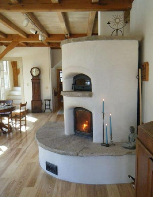 """This is a masonry heater. The firebox and air chambers are constructed to promote a super hot-burning fire. The result is twofold:  1) With a hotter fire, resins/sap are also burned, bringing the fuel-to-energy conversion to over 90% efficiency.   2) A masonry heater is surrounded by 4 to 6"""" of high thermal mass material that acts as a heat battery, absorbing all that extra heat and releasing it slowly over time. """""""