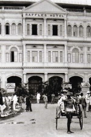 Historic image of a rickshaw driver and his passenger out front of the Raffles Hotel Singapore.