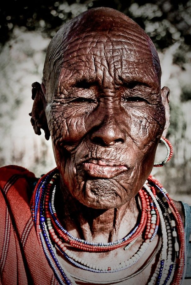 """Maralal, Northern Kenya. This photo of an old Samburu woman was taken in the outskirts of Maralal in Northern Kenya. Asking her about her age, all she could tell was that she was born in the year after the big drought. """"But age doesn't matter"""", she says. What matters is to have enough children, in order to keep a large herd of cattle."""