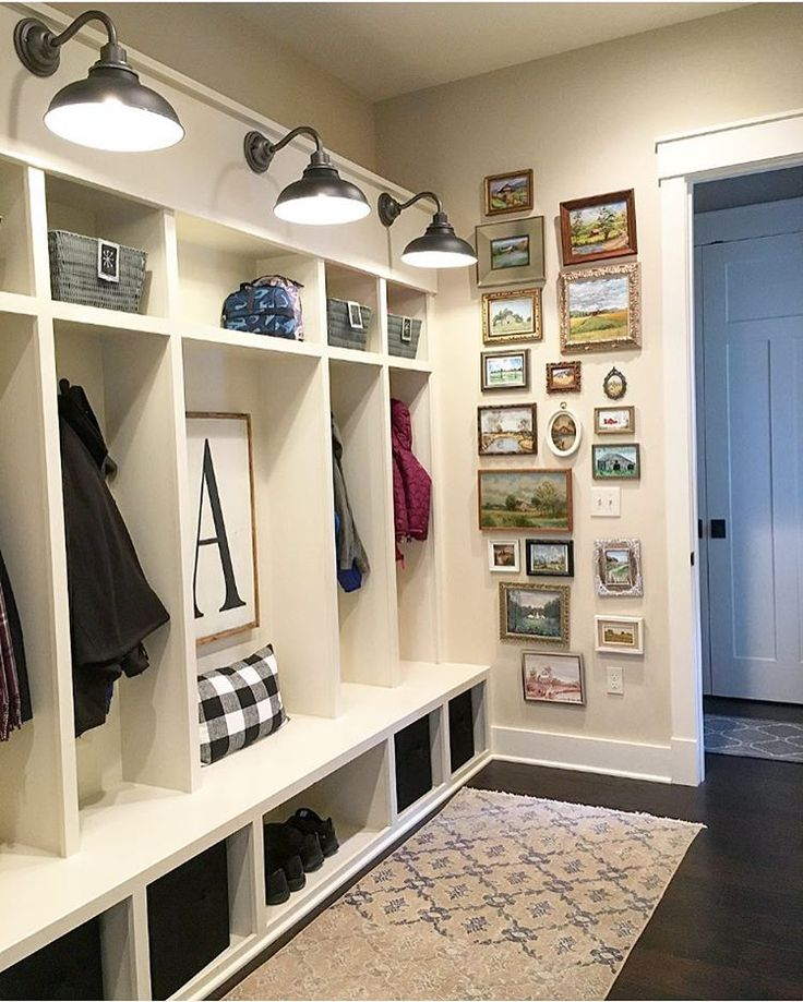 Farmhouse mudroom with built-in lockers, barn light wall sconces, a gallery wall of vintage paintings and an antique oushak runner. | See this Instagram photo by @farmhouseredefined