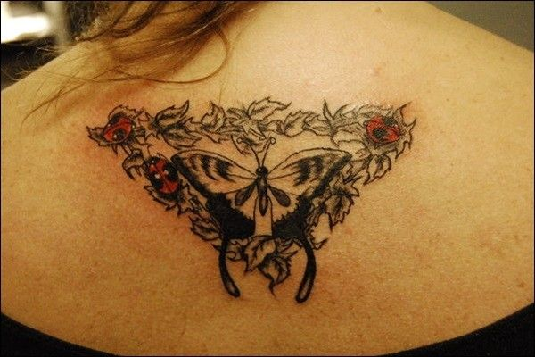 Red ladybugs and black butterfly tattoo on back