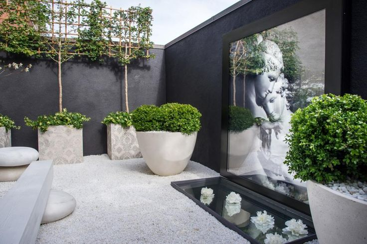 """Art consultant Alex Ray selected a photograph of Antonio Canova's Neoclassical sculpture of Psyche and Cupid at the Louvre as the centerpiece of """"An Ode to Innocence,"""" the private courtyard at the San Francisco Decorator Showcase 2015. Ray showcases the photo in a weatherproofed light box that doubles as a lighting source at night. Landscape architect Frank Eddy added floating peonies in the shallow pool to add to the romance of the setting."""