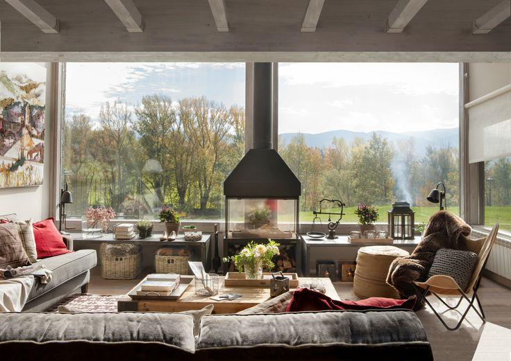 Salón rústico con chimenea de hierro y bancos bajo el gran ventanal (375655)