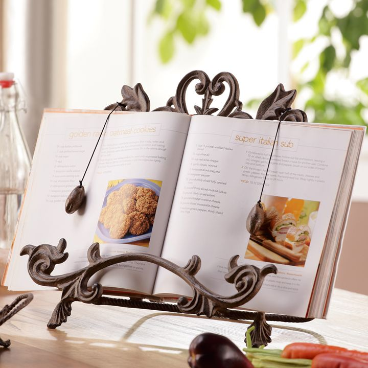 "Lacy and luxurious aluminum stand bears acanthus leaf front feet and a ""U"" shaped rear brace for balance. Vine ledge and page weights keep your cookbook in place. Fourteen inches wide and a foot tall...."