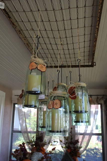 An old bed or crib spring bottom is used to suspend glass jar candleholders.