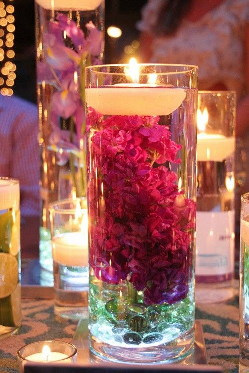 You can get the vases at Dollar Tree for $1 each. 3 bags of the rocks at $1 each, and the floating candles in a 6 pack for $2.99 at Hob Lob. With the flower, in the colors of the season, you've got yourself a very pretty, and very thrifty centerpiece!