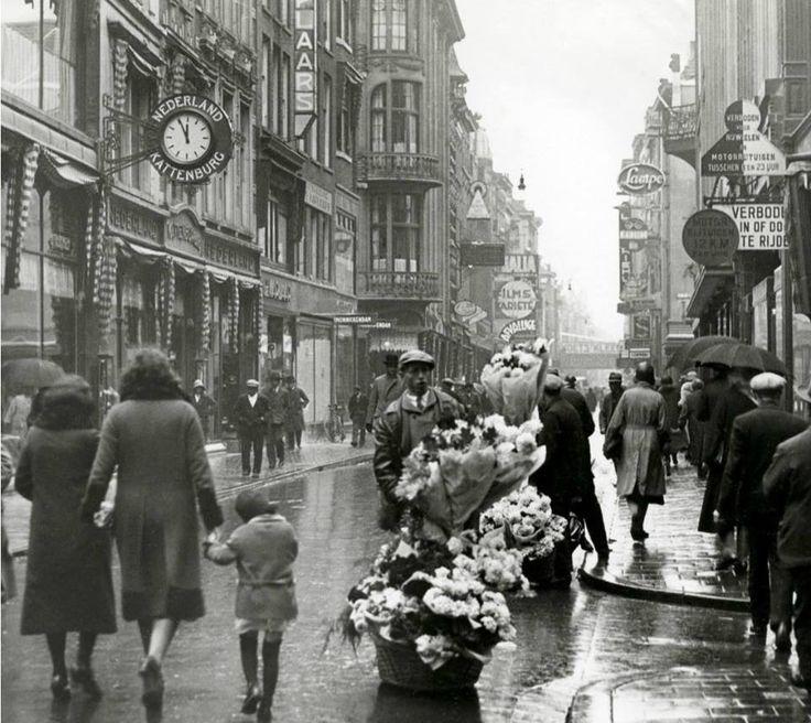 een regenachtige Hoogstraat in de jaren dertig, inclusief bloemenverkoper. De foto komt uit het archief van Spaarnestad.