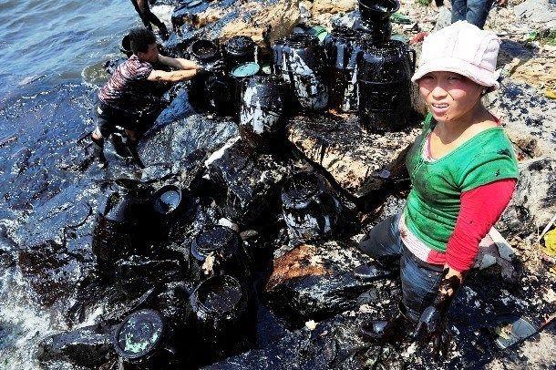 Mulher tenta conter o avanço do derramamento de petróleo perto de Dalian Port