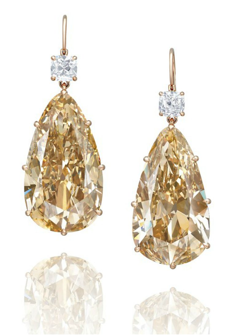 AN EXCLUSIVE PAIR OF COLOURED DIAMOND AND DIAMOND EAR PENDANTS  Each suspending a pear-shaped fancy brownish yellow diamond weighing approximately 28.65 and 28.27 carats, surmounted by a cushion-shaped diamond weighing approximately 0.94 carat and an old mine-cut diamond weighing approximately 0.86 carat, mounted in 18k rose gold, 4.7 cm long
