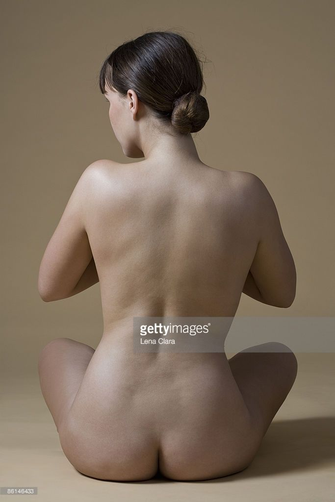 Rear view of a nude woman sitting crossed-legged : Stock Photo