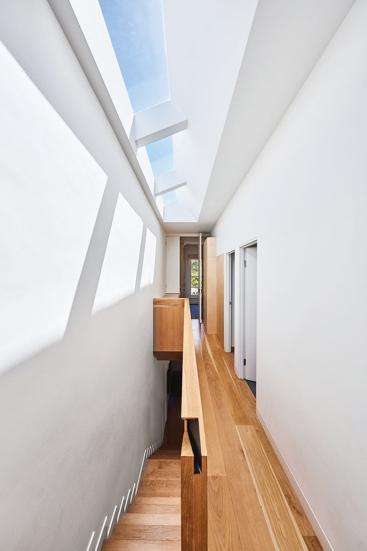Long, narrow skylights illuminate the American oak timber stairs, where a discreet hand-hold is crafted into the joinery. The laundry is hidden in cabinetry at the end of the hallway – an ironing board folds out on the left,