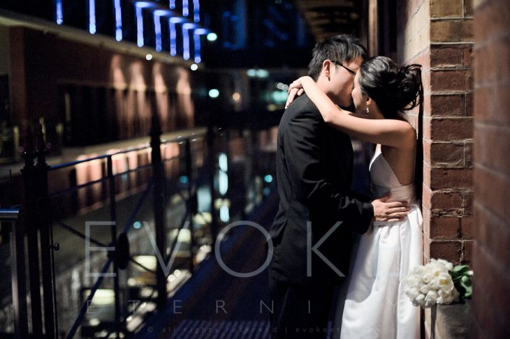 The couple's kiss under the light, like a scene from an old Hollywood movie.  Our wedding photography services in Australia can be viewed from http://www.evokeeternity.com/wedding-photography/