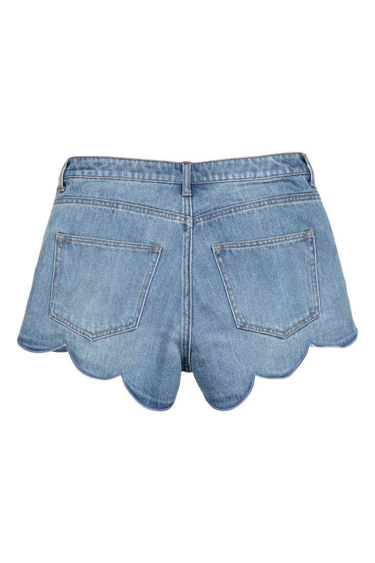 Short en jean: Short court en denim lavé avec bord festonné à la base. Modèle avec taille basse et braguette boutonnée.
