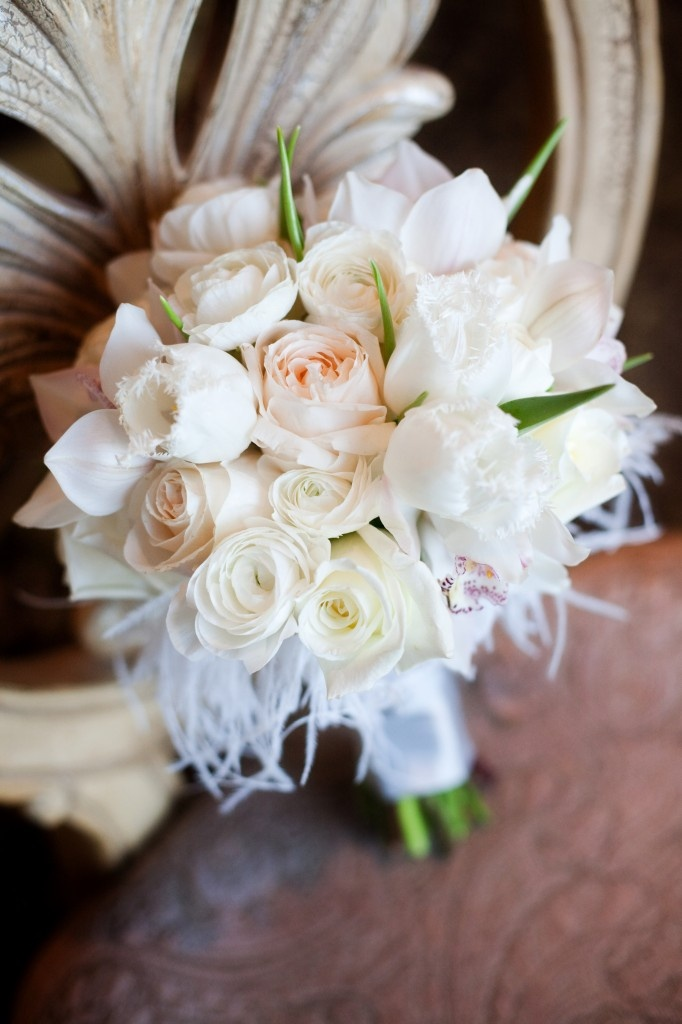White and cream garden roses, white fringed tulips, white cymbidium orchids and ranunculus with white feather trim.