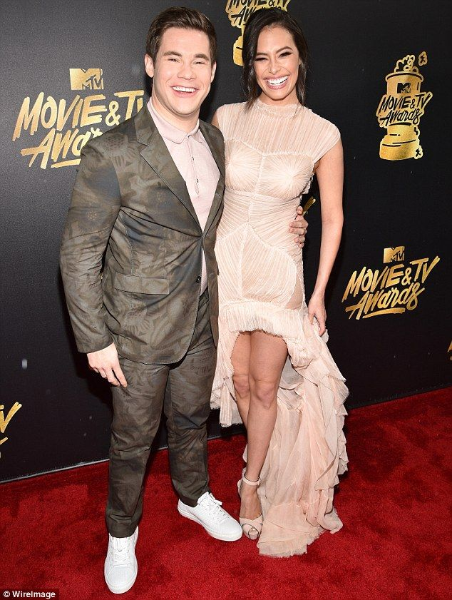 Happy host: Adam Devine beamed while holding onto girlfriend Chloe Bridges on Sunday at the MTV Movie And TV Awards in Los Angeles