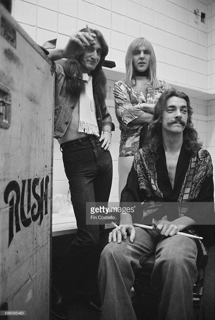 Canadian progressive rock group, Rush, backstage at the Civic Center in Springfield, Massachusetts, during the band's All The World's a Stage tour, 9th December 1976. Left to right: bassist Geddy Lee, guitarist Alex Lifeson and drummer Neil Peart.