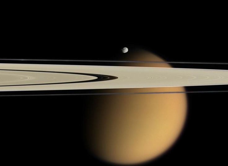 Saturn's orange moon Titan peeks from behind two of Saturn's rings. Small, battered Epimetheus, another of Saturn's 62 moons, appears just above the rings.