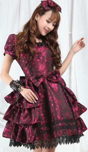 A pink and black shimmering gothic lolita dress with matching alice band.  It is short sleeved with black lace trim neckline and hem.  It is tiered to the back and sides and layered at the bottom for a fuller look.  It is lined with black petticoat and lace underskirts, finished with a detachable bow to the centre and a large tie bow to the rear.