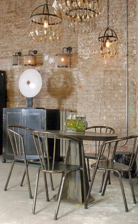Love the fancy chandeliers with the table, contrasting against the brick wall. I love the eclectic industrial style.
