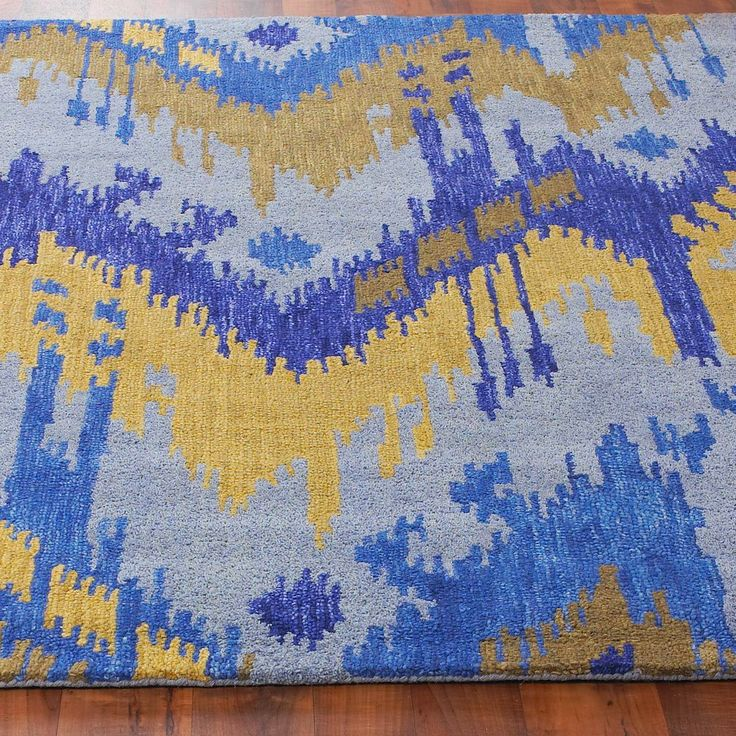 Flamestitch Ikat Rug A flamestick ikat rug in cooling hues of blues accented with golden yellows creates striking art work for your floor. Your eyes will love the interesting pattern and your feet will love the plush 100% hand tufted wool construction. Imported. (Specify size when ordering)
