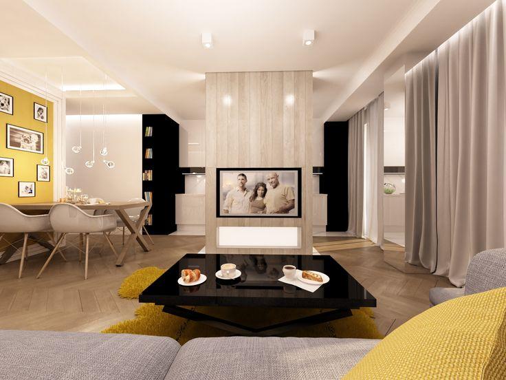 Salon z kuchnią. Czernie i biele  dopełniają ;dębowa podłoga, grafitowa kanapa , ciemno żółte  ściana jadalni,dywan , poduszki